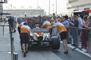 Force India wheels its car up the pit lane while fans watch on