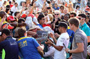 Lewis Hamilton signs autographs in the pit lane