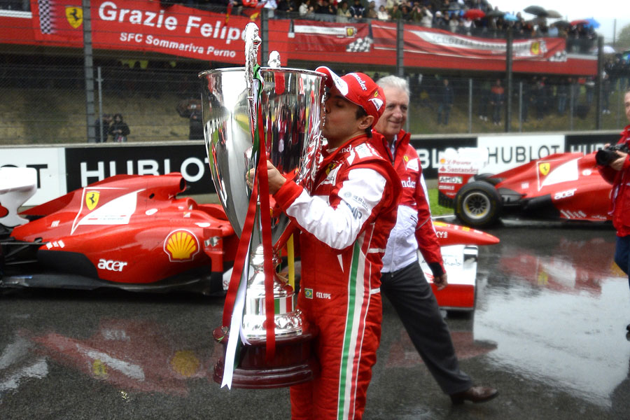 Felipe Massa kisses a 1.2 metre trophy presented to him by Ferrari to celebrate his career at the team