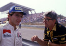 Ayrton Senna talks to Lotus team manager Peter Warr on the pit wall