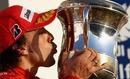 Fernando Alonso kisses a trophy