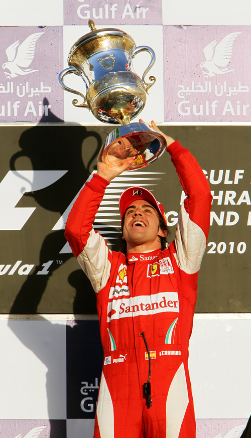 Fernando Alonso carries a trophy