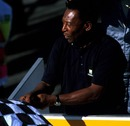 Football legend Pele mistakenly waves the chequered flag for Takuma Sato, one lap behind the leader