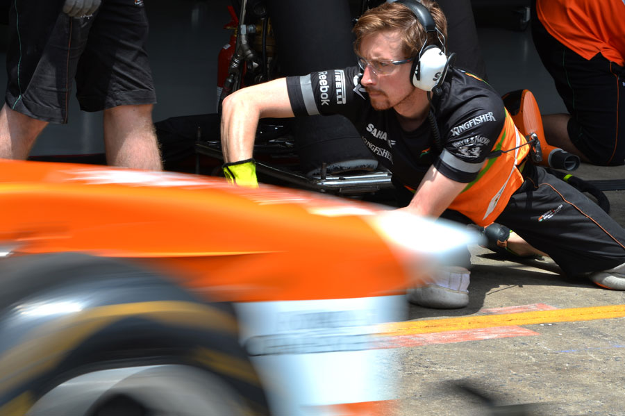 A mechanic focuses during a Force India pit stop
