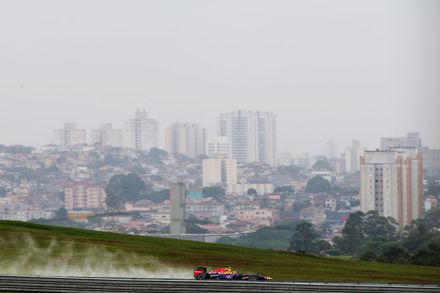 Mark Webber leaves a plume of spray during FP2