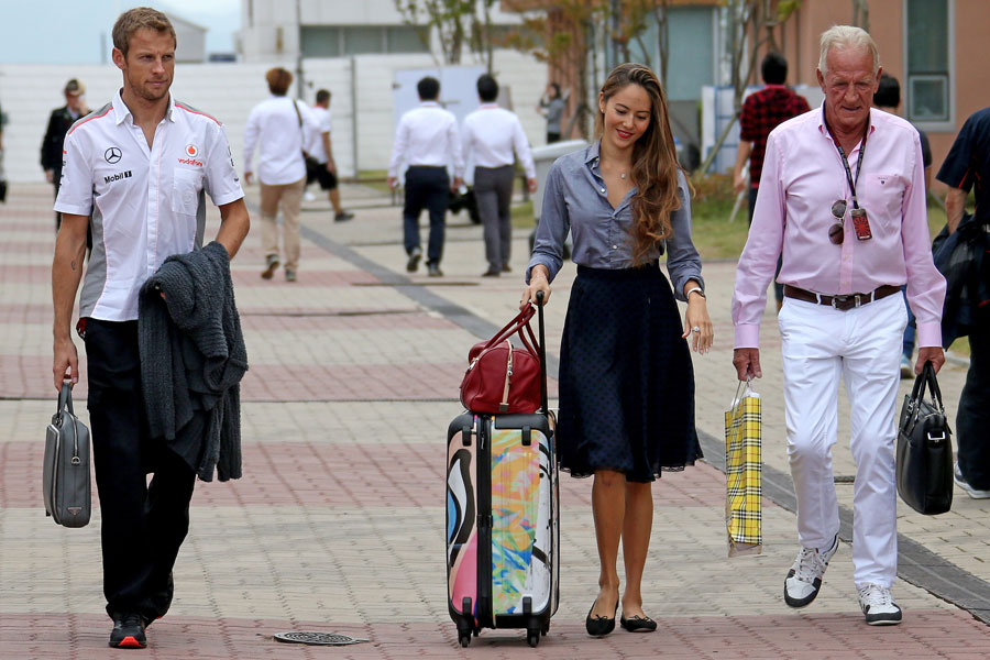 Jenson Button walks through the paddock with his girlfriend Jessica Michibata and father John