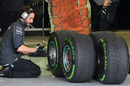A Mercedes employee inspects the Pirelli tyres