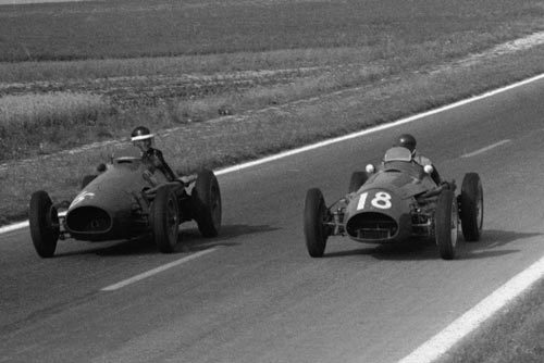 Hawthorn and Fangio exchange glances during the closing laps of their epic clash in the French Grand Prix