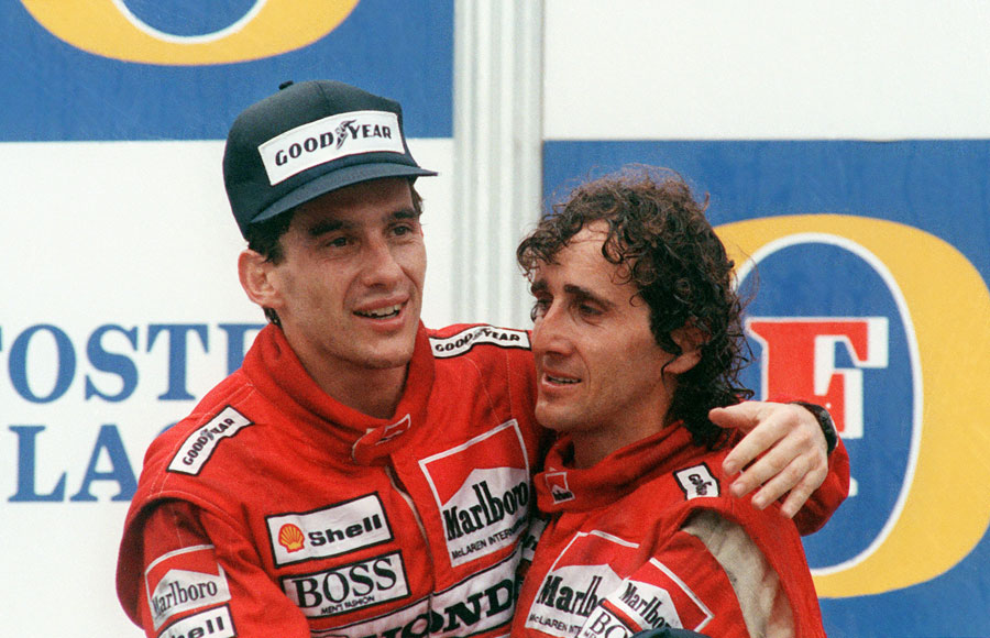 Ayrton Senna embraces his team-mate and race winner Alain Prost