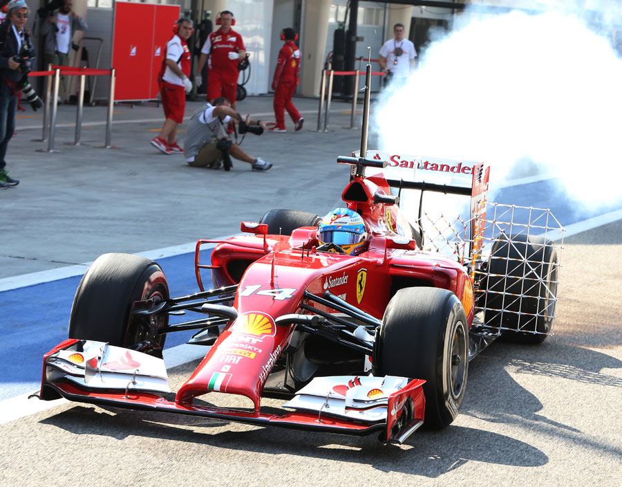 Fernando Alonso leaves the garage in a cloud of smoke