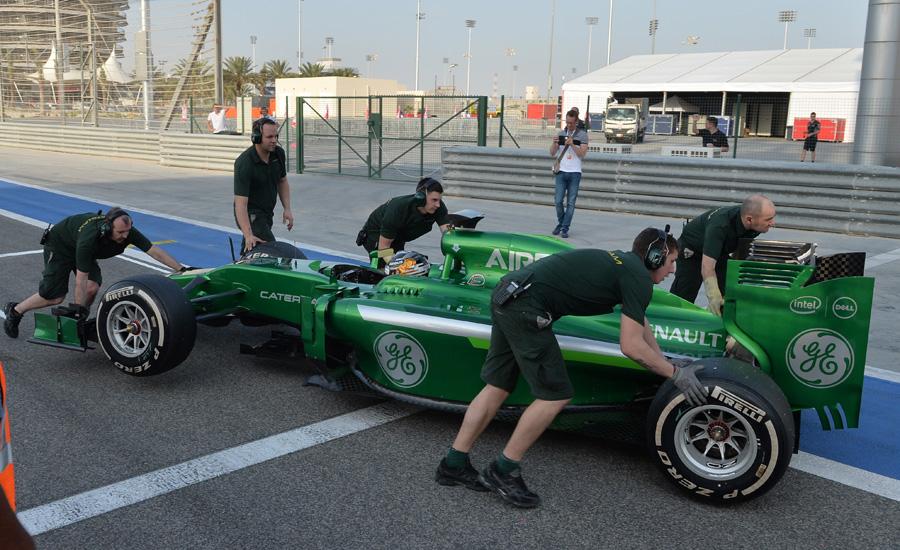 Kamui Kobayashi is wheeled away from the pit lane exit