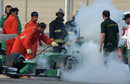 A marshall sees to Marcus Ericsson's Caterham with a fire extinguisher