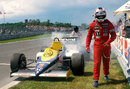 Nigel Mansell walks from his smoking Williams car