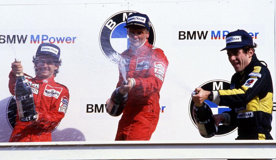 Niki Lauda celebrates his final career win alongside Alain Prost and Ayrton Senna