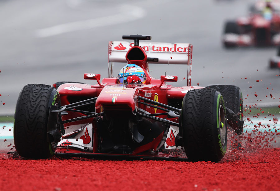 Fernando Alonso runs wide at Turn One after sustaining front wing damage