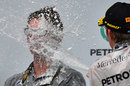 Nico Rosberg sprays Lewis Hamilton's race engineer Andy Shovlin on the podium