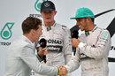 Actor Benedict Cumberbatch greets Lewis Hamilton before interviewing him on the podium