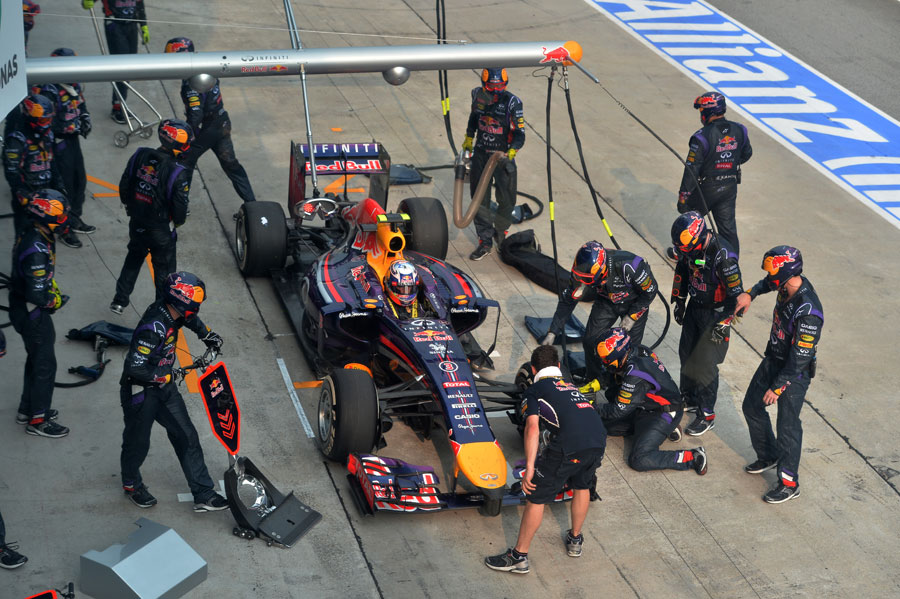 Red Bull's pit crew work on Daniel Ricciardo's car after his botched stop