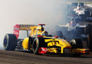 Robert Kubica emerges from the smoke of Mark Webber's Red Bull