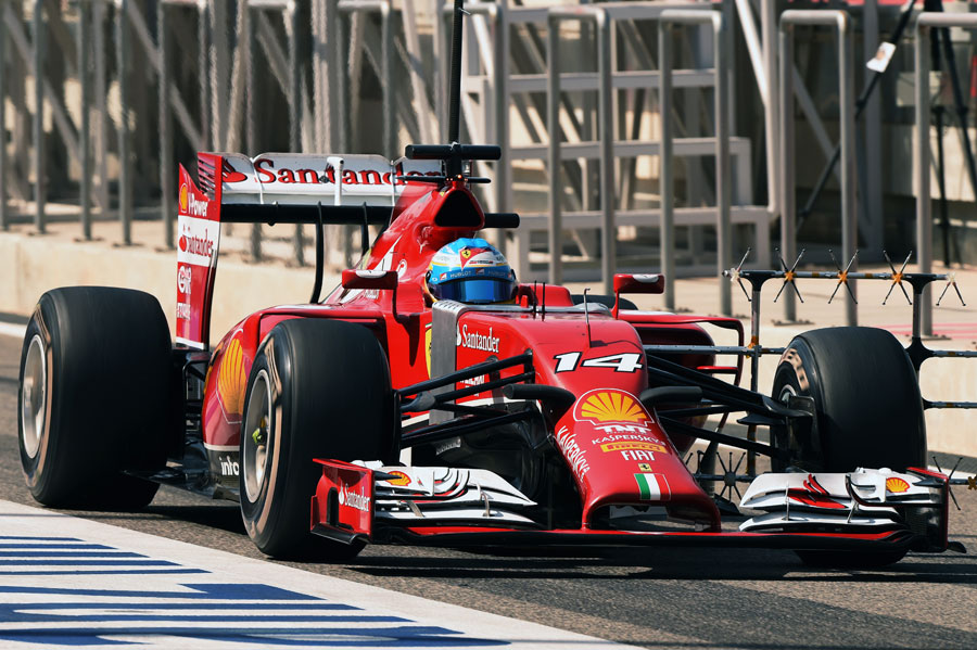 Fernando Alonso drives down the pit lane with an aero rig attached to his Ferrari