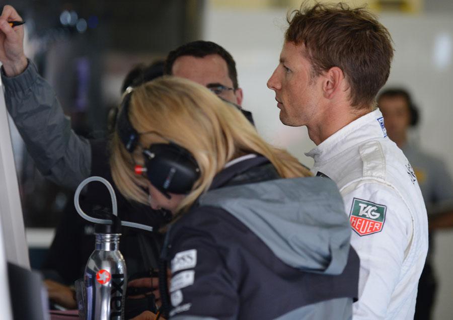 Jenson Button analyses data in the McLaren garage