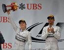Nico Rosberg hoists aloft his second-place trophy alongside race-winner Lewis Hamilton