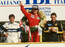 Alain Prost stands on the podium, flanked by Nelson Piquet and Ayrton Senna