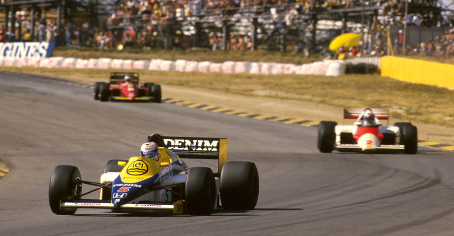 Nigel Mansell rounds a curve with Alain Prost in his rear-view mirrors