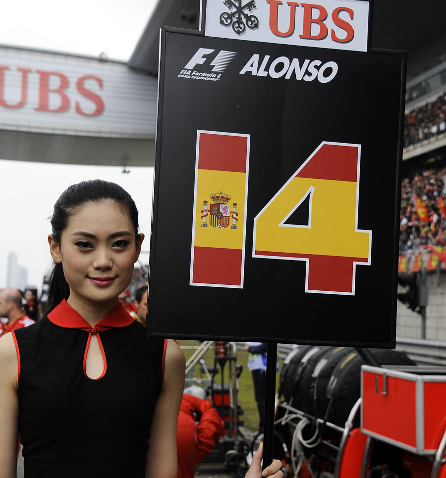 A grid girl stands alongside Fernando Alonso's grid slot