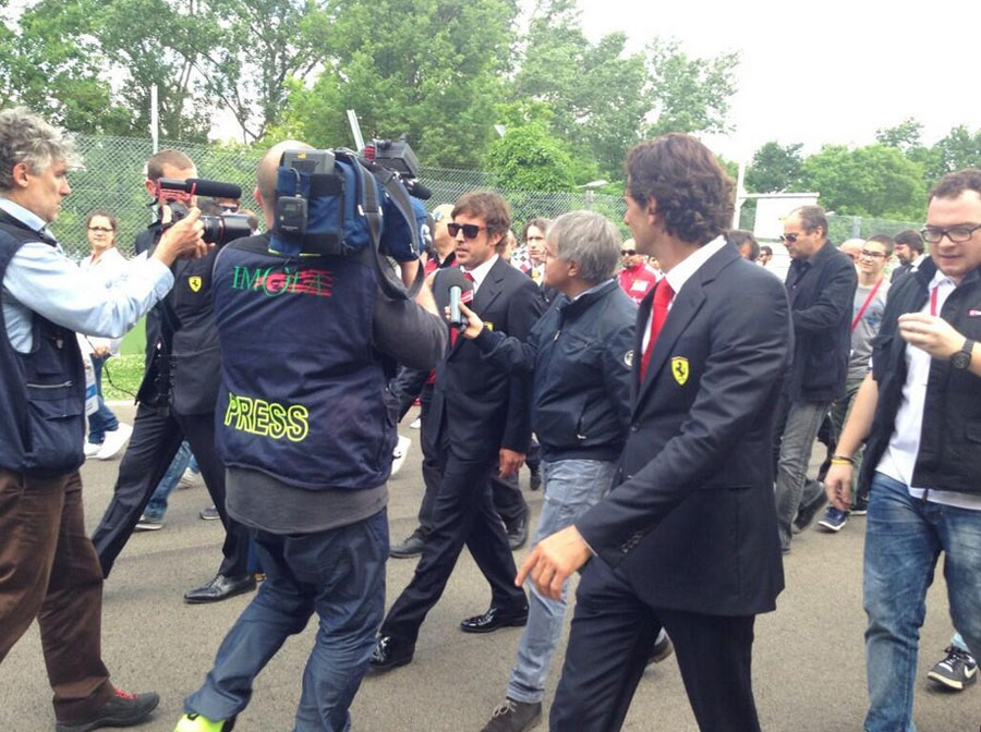 Fernando Alonso walks down to Tamburello, with Ferrari test driver Pedro de la Rosa watching on, during the Ayrton Senna memorial day at Imola