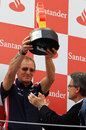 Williams race team manager Dickie Stanford lifts the winning constructors' trophy