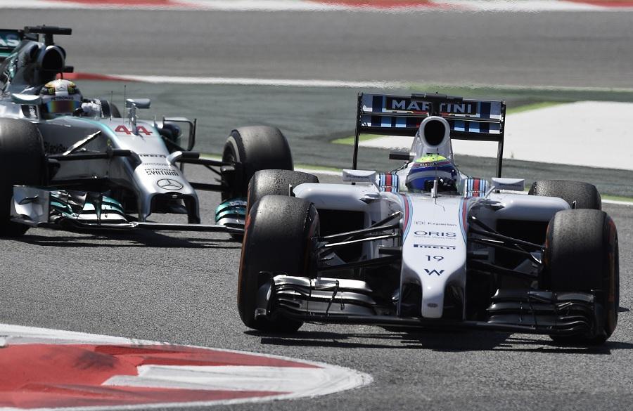 Williams driver Felipe Massa takes the corner ahead of Mercedes' Lewis Hamilton