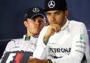 Nico Rosberg looks on as Lewis Hamilton talks in the post-race press conference