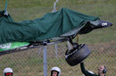 The remains of Kamui Kobayashi's Caterham is lifted away after he hit the barriers