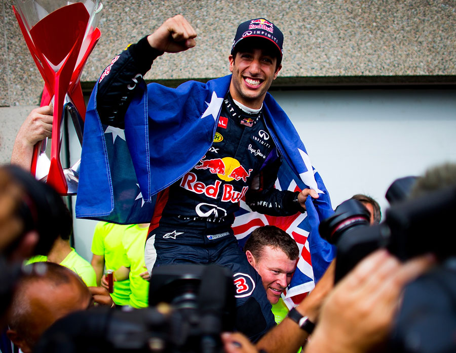 Daniel Ricciardo celebrates with the Red Bull team in the pit lane