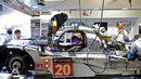 Mark Webber sits in the Porsche 919 Hybrid as mechanics try to get the car back on track