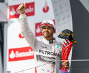 Lewis Hamilton acknowledges the crowd from the podium after his victory