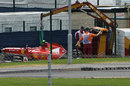 The wreckage of Kimi Raikkonen's Ferrari gets towed away after his first lap accident
