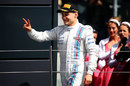 Valtteri Bottas gestures to Williams and the crowd as he arrives on the podium