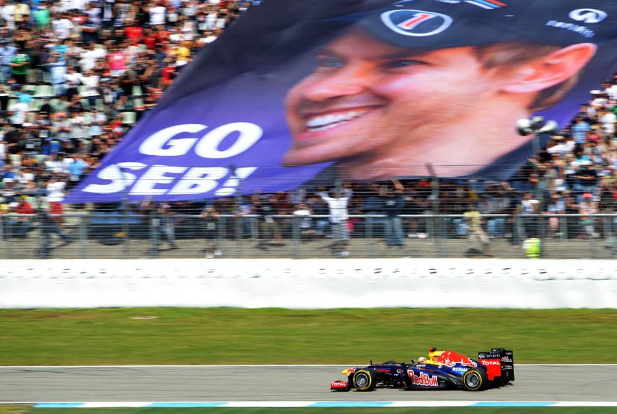 Sebastian Vettel roars past a banner of encouragement from his home fans