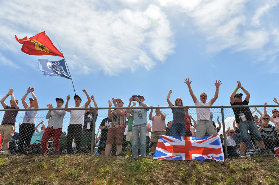 British fans celebrate Lewis Hamilton taking the lead