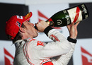 Jenson Button swigs champagne after his win