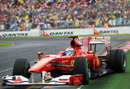 Fernando Alonso sildes his Ferrari right up to the crash barrier