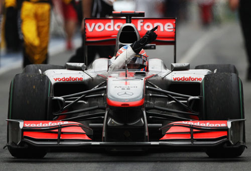 Jenson Button celebrates his win coming down the pit lane