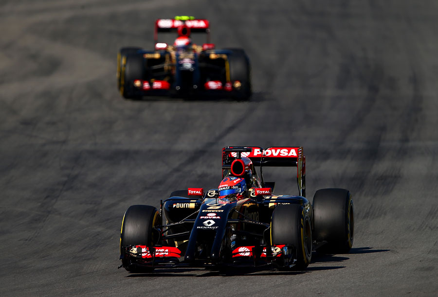 Pastor Maldonado enters a corner with team-mate Romain Grosjean in attendance