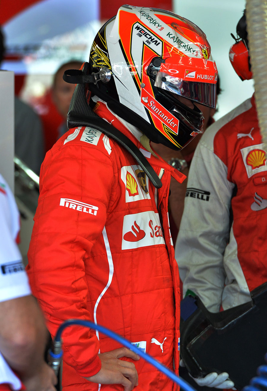 Kimi Raikkonen looks on in the Ferrari garage during qualifying
