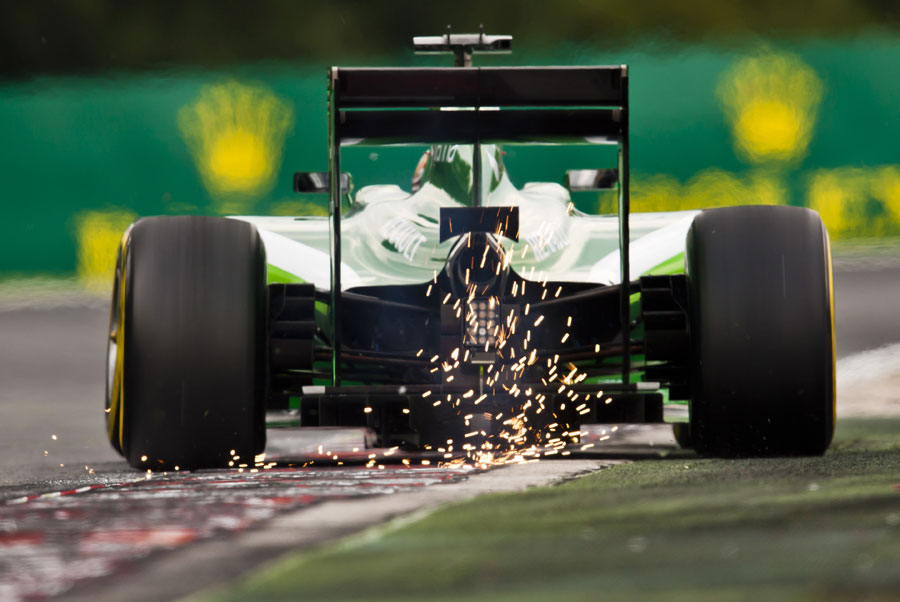 Kamui Kobayashi produces some sparks as he drives over the kerb
