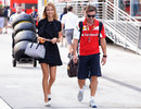 Fernando Alonso and his girlfriend Dasha Kapustina walk through the paddock