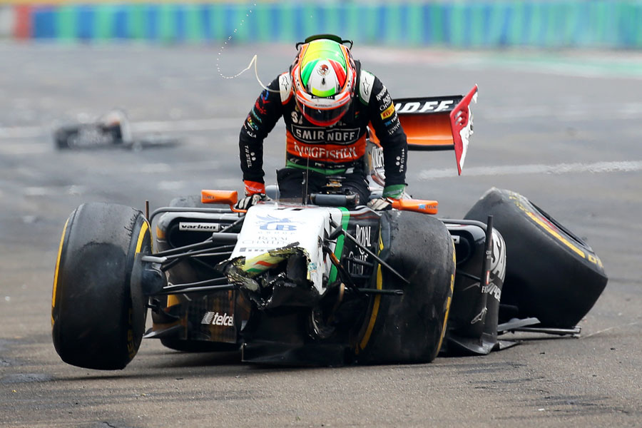 Sergio Perez clambers from his wrecked Force India