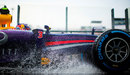 Daniel Ricciardo splashes through a puddle on his way to the grid